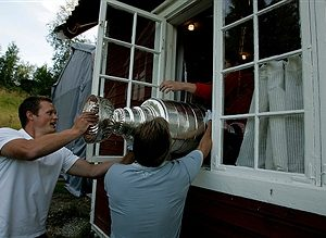 Gauthier, Robert –– – 128568.SP.0701.cup.RCG ––Sam Pahlsson and cup keeper Phil Pritchard, right, sneak the Stanley Cup into the back window at his Ornskoldsvik, Sweden home as friends and family gather for a party in the front yard, August 1, 2007.